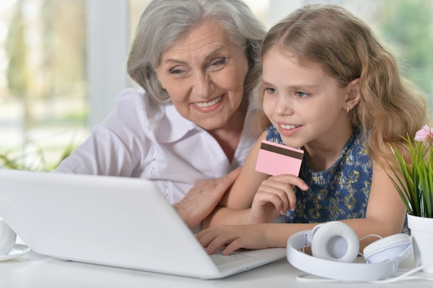Portret starej kobiety i małej dziewczynki korzystających z laptopa z kartą kredytową w rękach