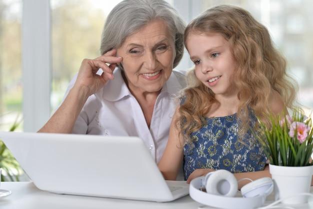 Portret starej kobiety i małej dziewczynki korzystających z laptopa