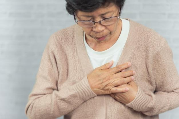 Portret starej kobiety mienia pierś przez zawału serca na szarość