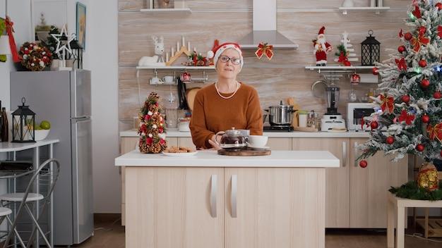 Portret starej kobiety w świątecznym kapeluszu świętującym boże narodzenie w udekorowanej kuchni