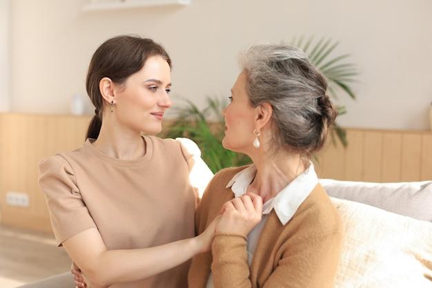 Portret starej matki i dojrzałej córki przytulanie w domu. szczęśliwa starsza mama i dorosła córka obejmując się miłością na kanapie.