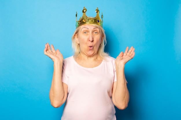 Portret starej przyjaznej kobiety o zdziwionej twarzy w swobodnej koszulce z koroną na głowie na odosobnionej niebieskiej ścianie. twarz emocjonalna