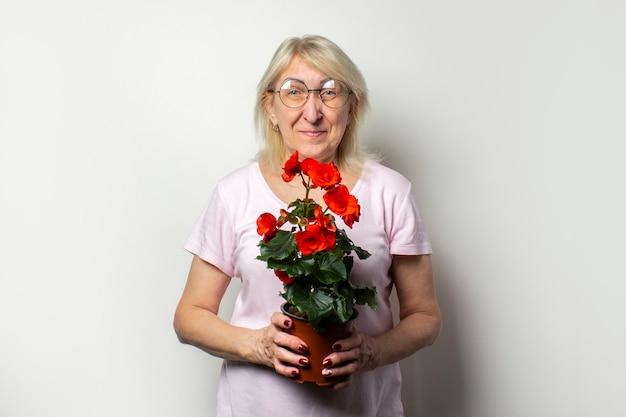 Portret starej przyjaznej kobiety w dorywczo t-shirt i okulary gospodarstwa kwiat pokoju na pojedyncze ściany światła. twarz emocjonalna. pojęcie pielęgnacji roślin, ogród przydomowy