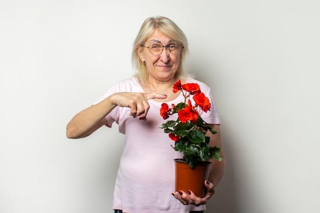Portret starej przyjaznej kobiety w swobodnej koszulce i okularach trzyma kwiat pokoju i wskazuje palcem na odosobnioną lekką ścianę. twarz emocjonalna. pojęcie pielęgnacji roślin, ogród przydomowy