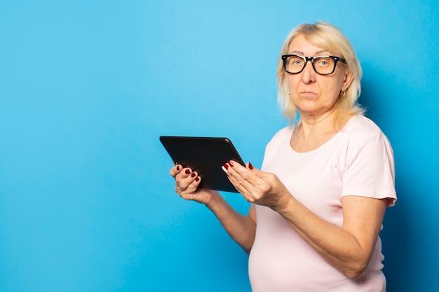 Portret starej przyjaznej kobiety z poważną twarzą w okularach i dorywczo t-shirt trzymając tabletkę w dłoniach na na białym tle niebieską ścianą. twarz emocjonalna