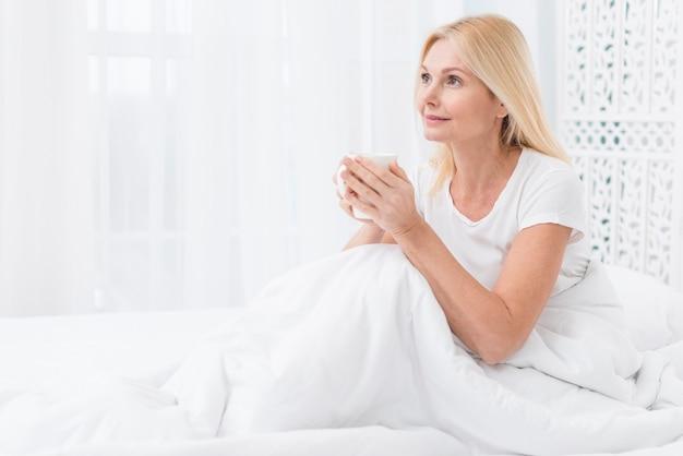 Portret starsza kobieta ma kawę w łóżku