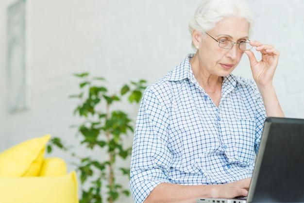 Portret starsza kobieta patrzeje laptop