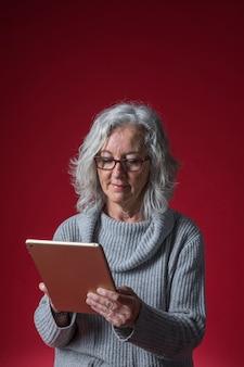 Portret starsza kobieta używa cyfrową pastylkę przeciw czerwonemu tłu
