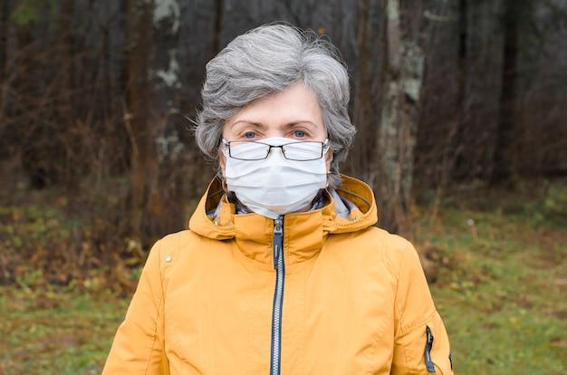 Portret starsza kobieta w okularach i masce medycznej. starszy kobieta w masce ochronnej patrząc w kamerę, na zewnątrz.