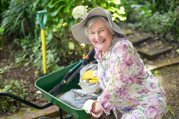 Portret starsza kobieta z wheelbarrow w ogródzie