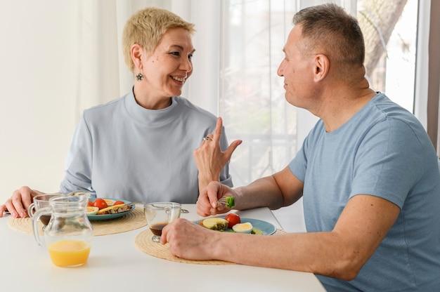 Portret starsza para rodzinny obiad w domu jedzenie zdrowego śniadania, uśmiechając się i patrzy na każdego