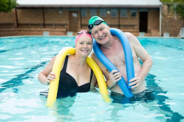Portret starsza para trzyma makaron w basenie