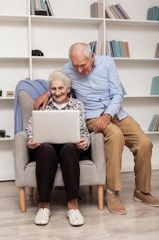 Portret starsza para używa laptop