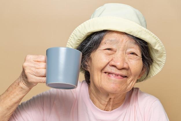 Portret starszego azji południowo-wschodniej kobiety trzymającej szary kubek kawy.