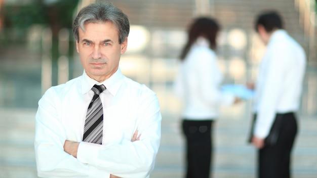 Portret starszego biznesmena na rozmytym tle office.photo z miejsca na kopię