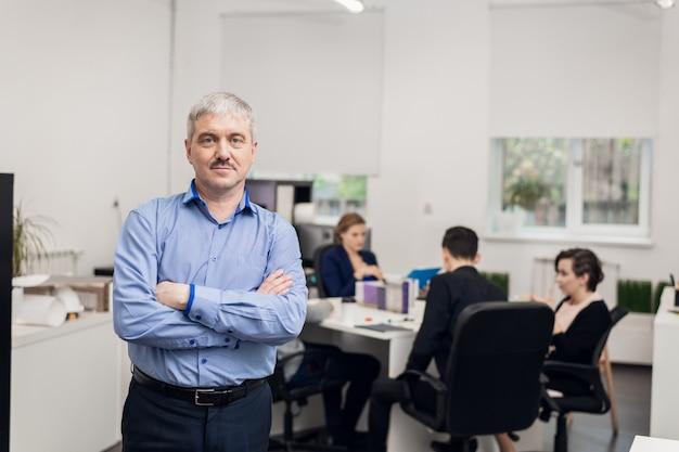 Portret starszego biznesmena stojącego w jego biurze