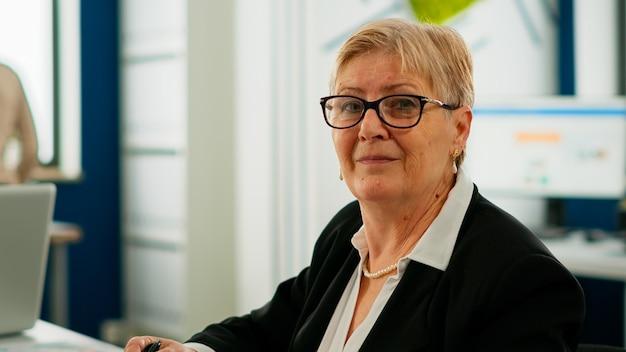Portret starszego businesswoman patrząc na kamerę siedzi w pokoju burzy mózgów, przygotowując się do spotkania z partnerami. manager pracujący w profesjonalnym biznesie finansowym typu start-up gotowy na konferencję