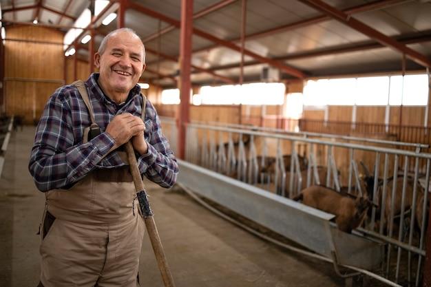 Portret starszego cattleman z widłami stojący w gospodarstwie