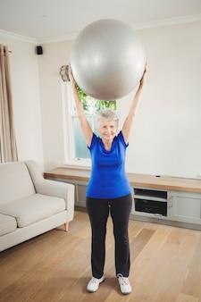 Portret starszego kobieta podnoszenia piłki do ćwiczeń podczas ćwiczeń w domu