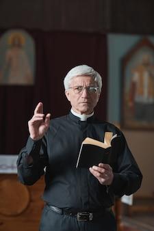 Portret starszego księdza czytającego biblię podczas mszy w kościele