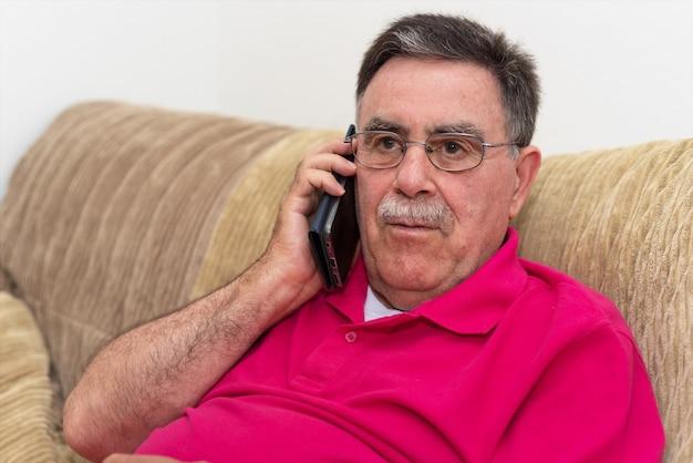 Portret starszego mężczyzna poważny wyrażenie opowiada na telefonie