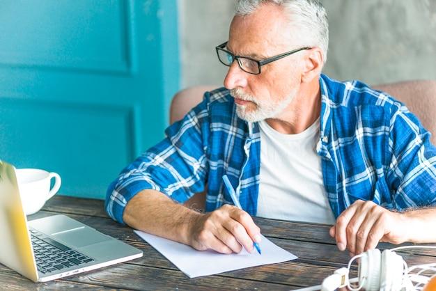Portret starszego mężczyzna writing notatki używać laptop na stole
