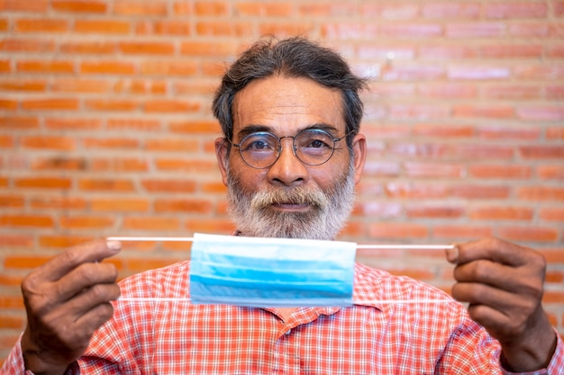 Portret starszego mężczyzny gotowy do noszenia maski ochronnej w celu ochrony przed covid-19