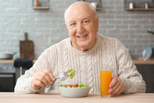 Portret starszego mężczyzny jedzącego obiad w domu