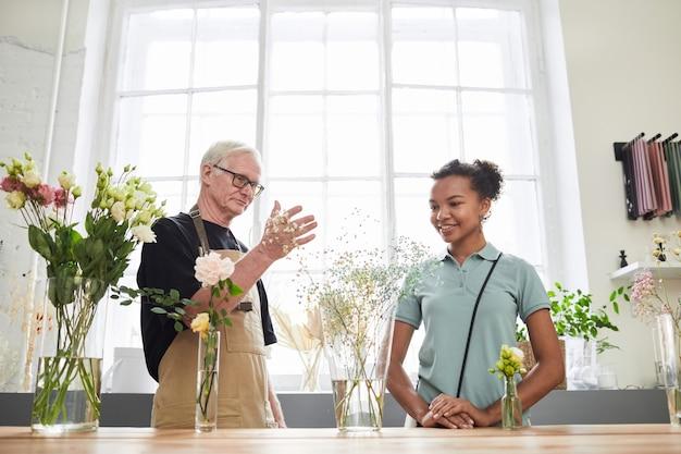 Portret starszego mężczyzny konsultującego się z młodą kobietą podczas pracy w kwiaciarni