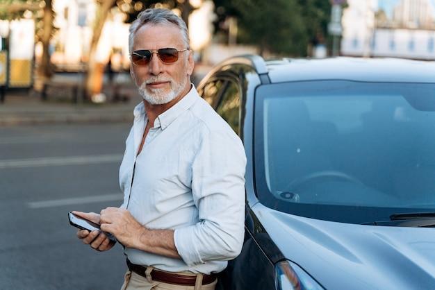 Portret starszego mężczyzny na zewnątrz. mężczyzna w średnim wieku stojący obok swojego samochodu typu suv suv