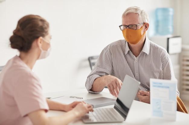 Portret starszego mężczyzny noszącego maski podczas rozmowy z lekarzem lub pielęgniarką w klinice medycznej, skopiuj przestrzeń
