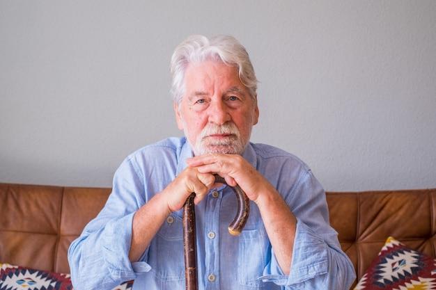 Portret starszego mężczyzny opierając się na lasce siedząc na kanapie. samotny starszy mężczyzna siedzi w salonie w domu. staruszek z siwymi włosami oparty na lasce, siedzący na kanapie w domu