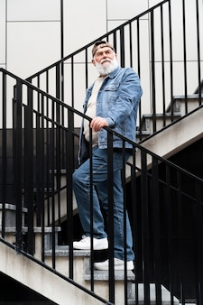 Portret starszego mężczyzny pozowanie na schodach na zewnątrz w mieście