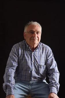 Portret starszego mężczyzny siedzącego na czarnej przestrzeni