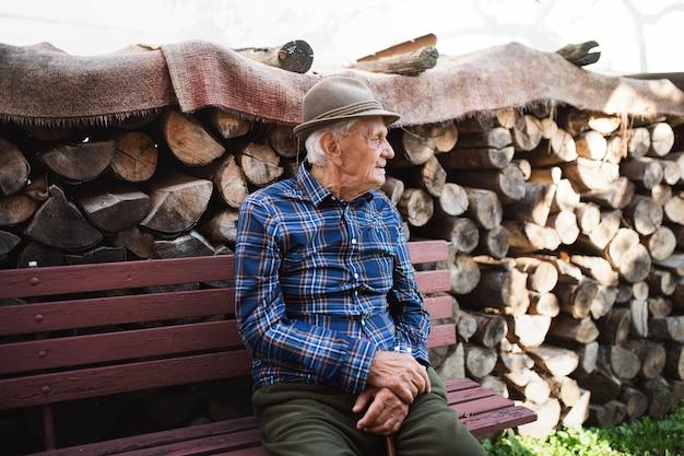 Portret starszego mężczyzny siedzącego na ławce na zewnątrz w ogrodzie, odpoczynek.