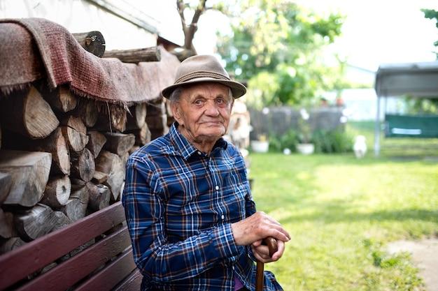 Portret starszego mężczyzny siedzącego na ławce na zewnątrz w ogrodzie, odpoczywając i patrząc na kamery.