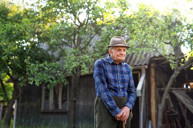 Portret starszego mężczyzny stojącego na zewnątrz w ogrodzie, odpoczynek.