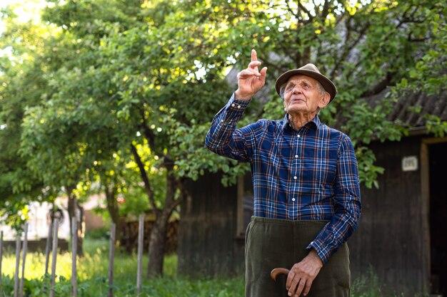 Portret starszego mężczyzny stojącego na zewnątrz w ogrodzie, patrząc w górę.