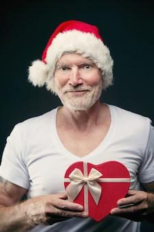 Portret starszego mężczyzny w kapeluszu santa clause w siłowni, trzymając prezent w jego rękach koncepcja bożonarodzeniowa