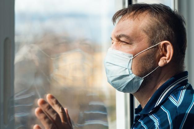Portret starszego mężczyzny w maski medyczne. starszy mężczyzna w domu wygląda przez okno podczas kwarantanny. koronawirus, wybuch covid-19.