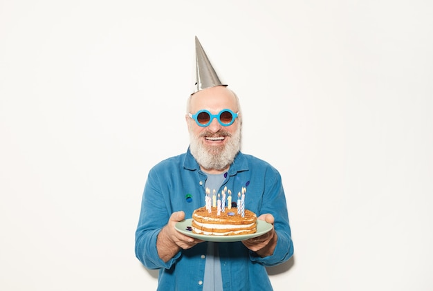 Portret starszego mężczyzny w strona kapelusz i okulary przeciwsłoneczne, trzymając tort urodzinowy i uśmiecha się do kamery na białym tle