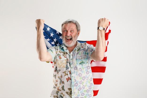 Portret starszego mężczyzny z flagą stanów zjednoczonych ameryki na białym tle na białym studio