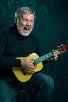 Portret starszego mężczyzny z gitarą.