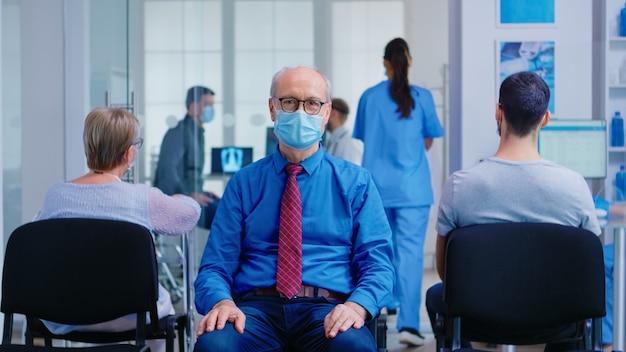 Portret starszego mężczyzny z maską na twarz przed koronawirusem w poczekalni szpitala patrząc na kamery. pacjenci podczas epidemii chrząstki w klinice oczekujący na badanie.
