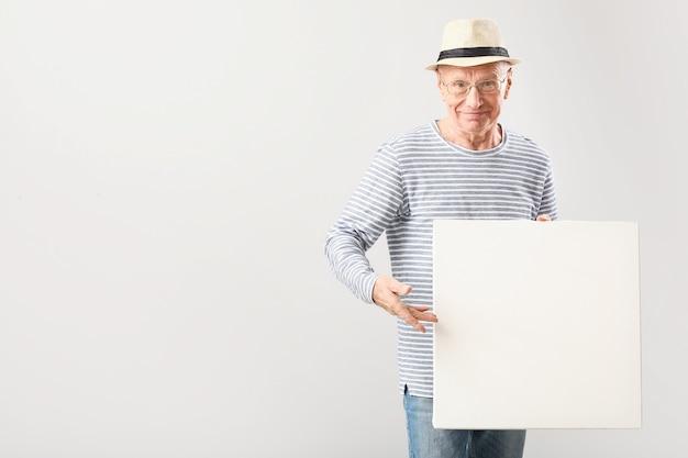 Portret starszego mężczyzny z pustym plakatem na szaro