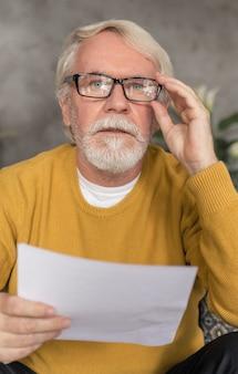 Portret starszego mężczyzny z siwymi włosami i brodą, patrzącego na kamerę trzymającą rachunek kredytowy lub rachunek za media