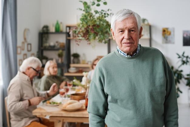 Portret starszego mężczyzny z siwymi włosami patrzącego na kamerę z przyjaciółmi siedzącymi przy stole w tle