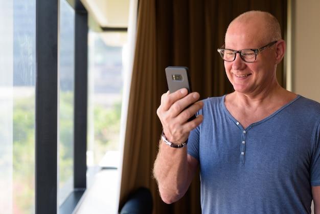 Portret starszego przystojnego mężczyzny skandynawskiego relaks w sypialni hotelu