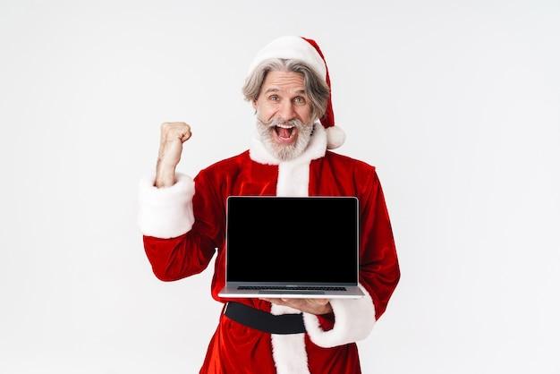 Portret starszego siwego mężczyzny świętego mikołaja w czerwonym stroju trzymającego otwarty laptop na białym tle