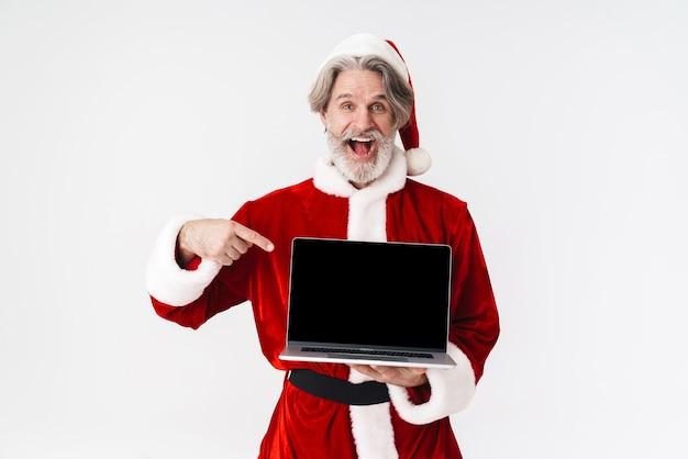 Portret starszego siwowłosego mężczyzny świętego mikołaja w czerwonym stroju wskazującym palcem na otwartym laptopie na białym tle
